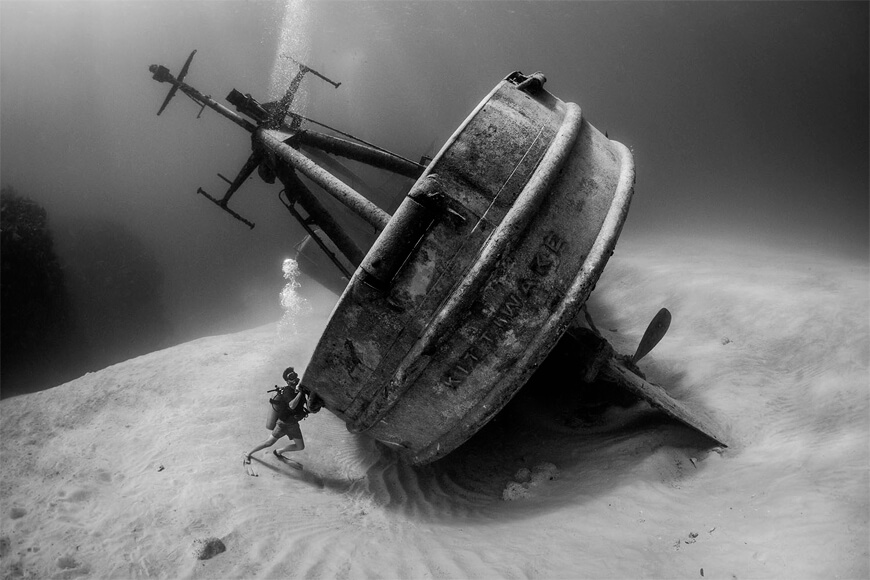"Highly Commended, Wrecks. ""For six years, the 251-foot-long USS Kittiwake sat upright where it was sunk as an artificial reef. On October 8, 2017, it was discovered that powerful surge from passing hurricane Nate had rolled the ship onto its side. I raced to find a dive operator to take me out there, and was able to dive and document the shipwreck the very next day. I was showing those initial photographs to my husband and my friend when I had an idea: 'Wouldn't it be funny if a diver with Obsessive Compulsive Disorder (OCD) was so bothered by the ship being on its side that they tried to right it?' The idea for a photograph was born! My friend Simon Claeys modeled for me in the photograph. In order to make it look authentic, Simon actually 'attempted' to push the ship upright. The bubbles in the photograph are from his effort."" Photographed near Grand Cayman, Cayman Islands."